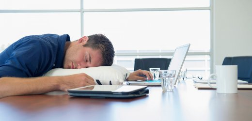 Over-worked business executive sleeping at desk