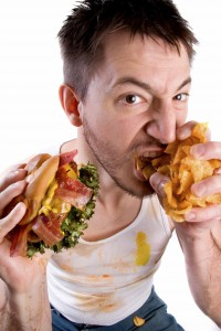 He's got his game face and game food on... messy guy cramming his face full of burger and chips.